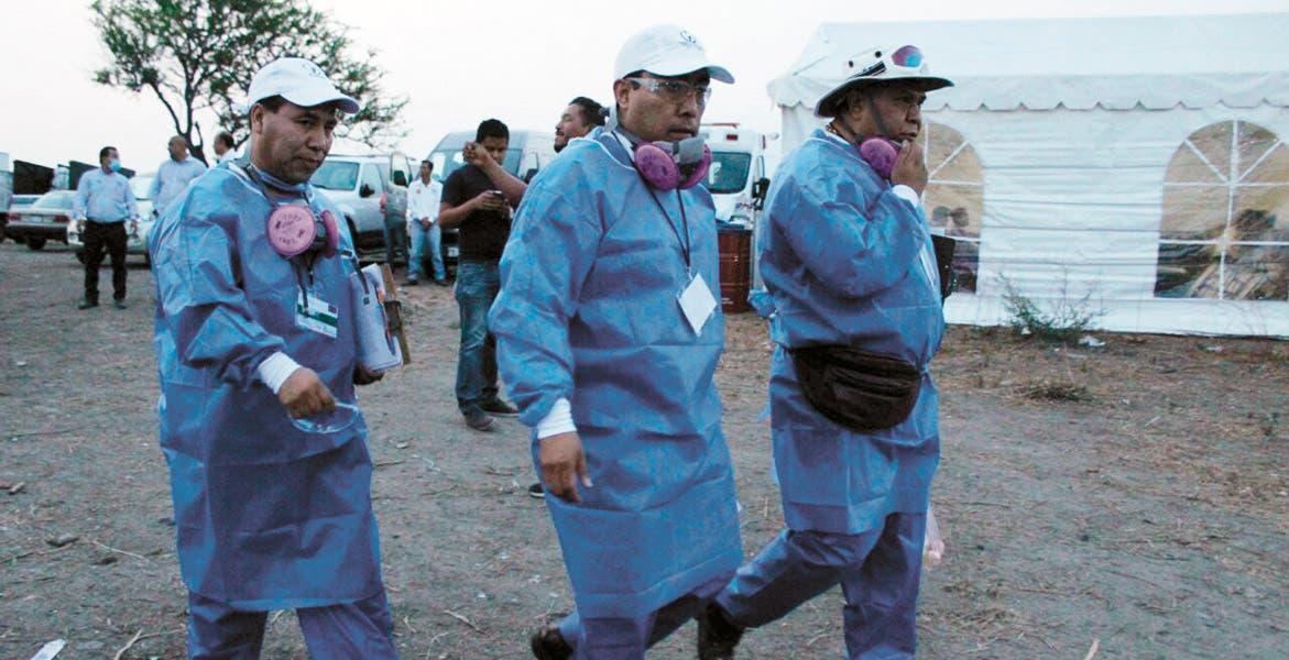 Vigilan. Persona de la Comisión Nacional de Derechos Humanos (CNDH) participan como observadores en la exhumación.