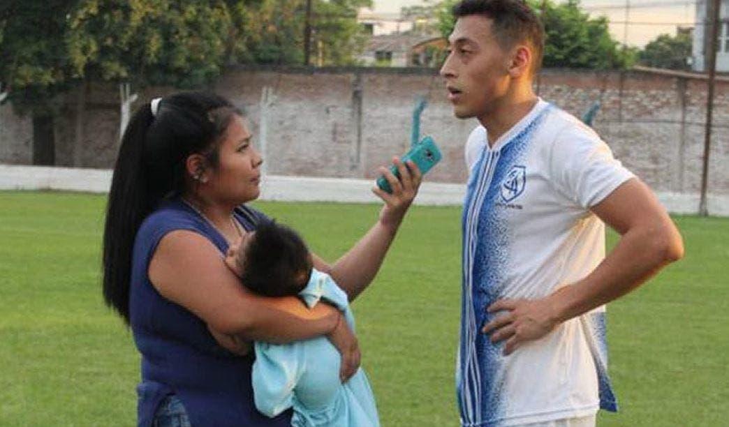 Con bebé en brazos, mujer periodista cubre partido de futbol