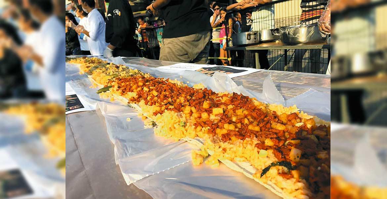 Con la participación de jóvenes de distintas universidades se llevó a cabo la eleboración del tradicional 'Taco Acorazado', delicia culinaria de la cocina tlahuica; el taco gigante midió 61 metros de largo y fue repartido entre los asistentes.