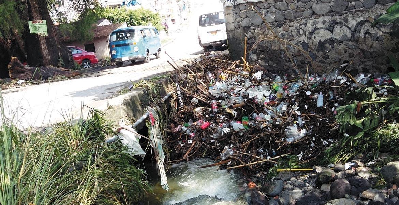En acción. Personal de PC Temixco hace hincapié a la población en no tirar desechos en ríos, canales o barrancas debido al riesgo que ello conlleva ante las lluvias.