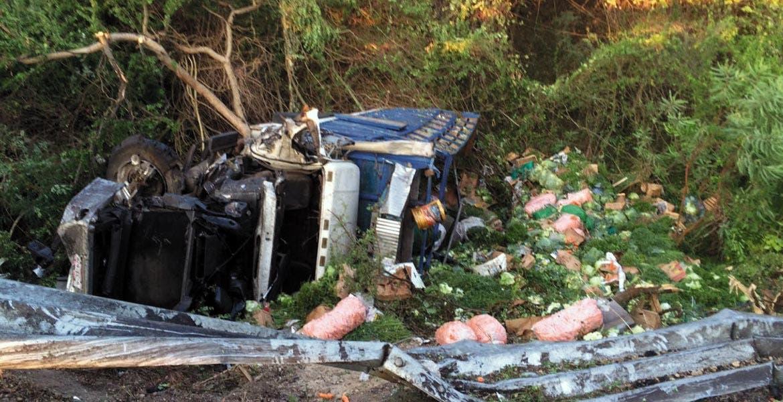 El vehículo. Así quedó el camión cargado con verduras, luego de que el chofer perdiera el control, chocara contra la valla de contención, se saliera del camino y volcara.