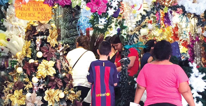 Búsqueda. Decenas de familias recorren tiendas y negocios en busca de pinos baratos, así como adornos, para gastar poco en está Navidad.