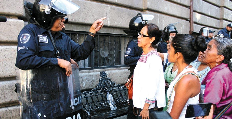 En la mañana. Un policía le indica a las comerciantes de artesanías que ya no se podrán instalar frente a Correos.