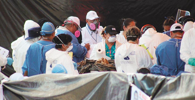 Periciales. Peritos de la PGR, Fiscalía, de la CNS y de la UAEM, toman las muestras al primer cadáver exhumado de las fosas.