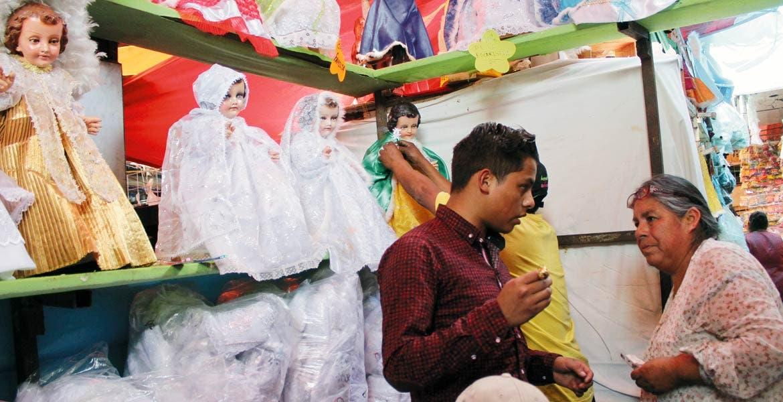 Comercio. Ayer decenas de personas acudieron al mercado para comprar sus ropones y otros accesorios para vestir al Niño Jesús.