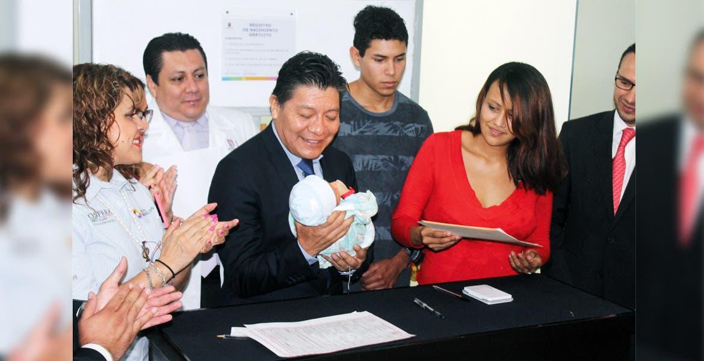 En marcha. El secretario de Gobierno, Matías Quiroz Medina, sostiene al bebé de la familia Arteaga Flores, el primero en contar con su registro de nacimiento digitalizado en la entidad.