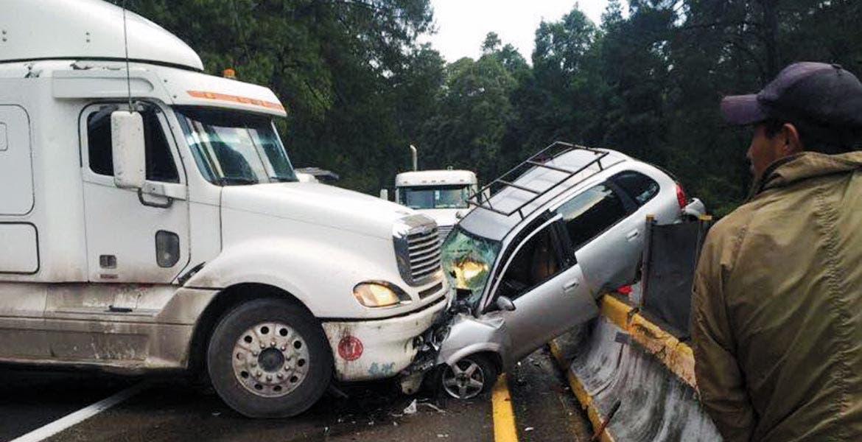 Aparatoso. El tráiler impactó al Chevy y acabó arrastrándolo hasta terminar subiéndolo a la barra de contención, donde el conductor del minauto quedó prensado.