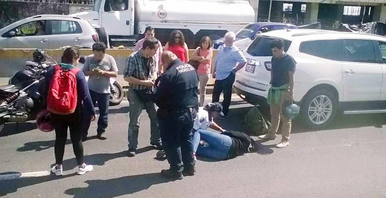 Auxilio. Juan Pablo y Liliana resultaron lesionados al derrapar en su moto, presuntamente debido al exceso de velocidad con que circulaban y la tierra regada en la pista.