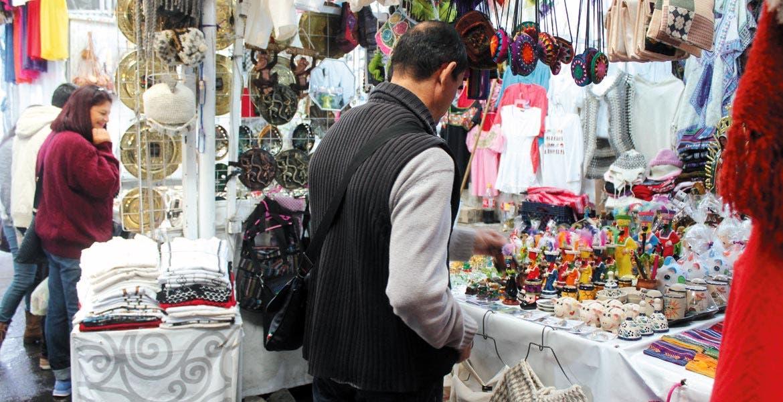 Turista comprando algunas piezas dentro del mercado de las artesanías y la plata