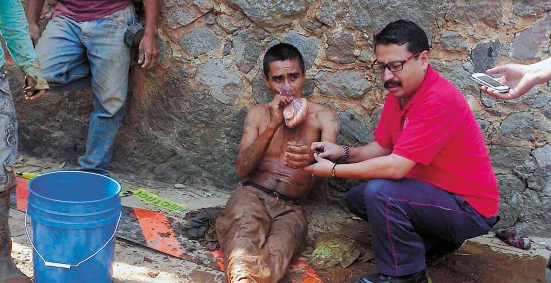 Atención. Uno de los empleados muerde un bolillo para el susto mientras es revisado por personal de Protección Civil, tras ser rescatado al quedar sepultado en la zanja.