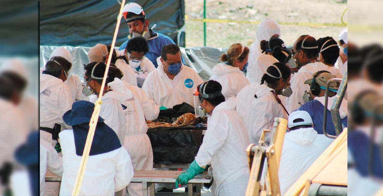 Labores. Peritos de la PGR, Comisión Nacional de Seguridad, Fiscalía General del Estado y de la UAEM, examinan en la mesa de trabajo y toman muestras a uno de los 11 cadáveres que fueron exhumados de las fosas de Tetelcingo, en Cuautla.
